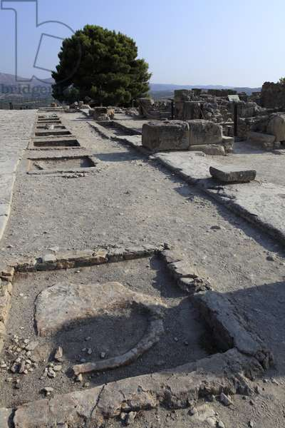 """Minoan archeological site of Phaistos. General view of the west wing shrines along the central court from the north wing. There were two types of shrine: """"Bench shrine"""" and """"Lutral Basin"""""""". The """""""" bench Shrine"""""""" was a small and rectangular room with low benches running round the walls to support cult objects and figurine of the deity. On some of them were found female figurine, ritual vessels, and """""""" offering tables"""""""" (small altar). The """""""" Lustral Basin"""""""" type was a room lower than the founding structures, with a few steps leading down into them. It was used for purification rituals."""
