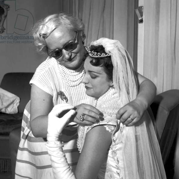 Milan, 1953. Fashion designer Jole Veneziani tries on a wedding dress worn by Liuba Rosa future lady Rizzoli.