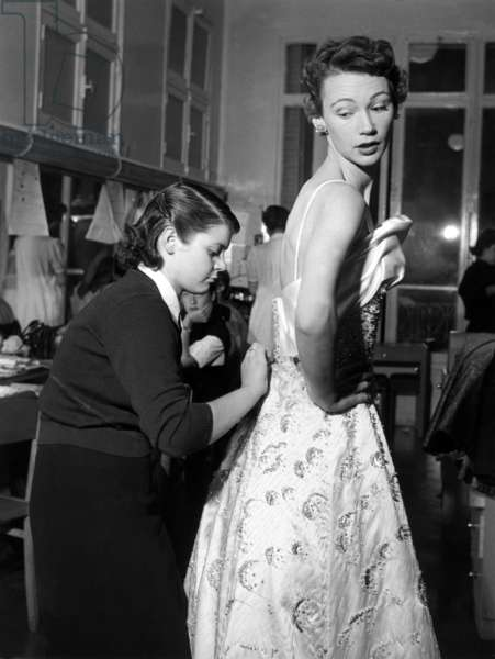Paris, November 1952. Model Sophie Malga' rehearses with the seamstress in dress before a fashion show