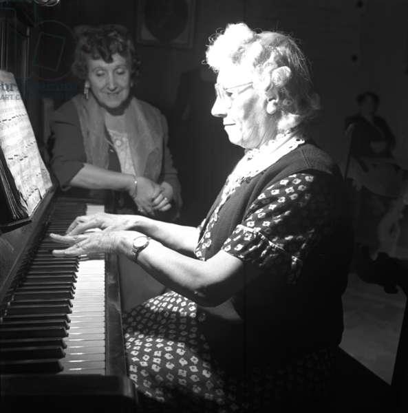 Milano, 1954. La casa di riposo per musicisti Fondazione Giuseppe Verdi. Anziane ospiti al pianoforte