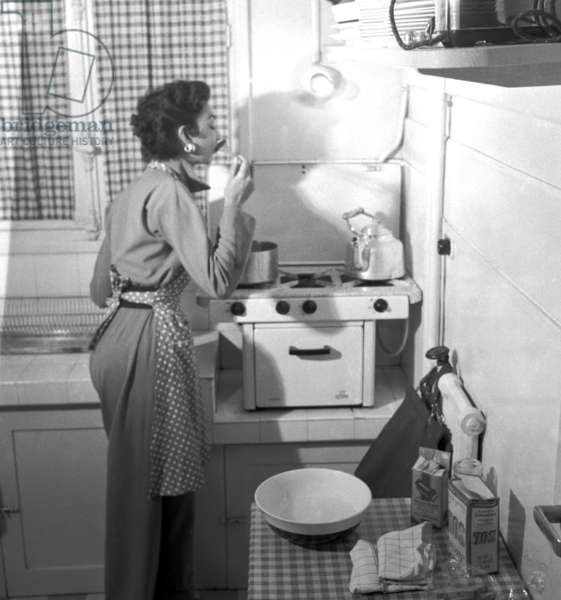 Fashionable. Paris, 1952. Model Teresita Montez, sister of the most famous actress Maria Montez, in the kitchen of her home. This reportage has been published on number 49 of the European with the text written by Manlio Cancogni