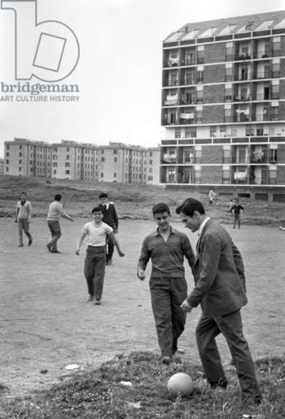 Pier Paolo Pasolini plays football with boys from the township of Centocelle, Italy, 1960 (b/w photo)