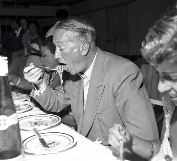 Viareggio, 1952. Actor and singer Maurice Chevalier struggling with a plate of spaghetti at a dinner for the Viareggio Prize