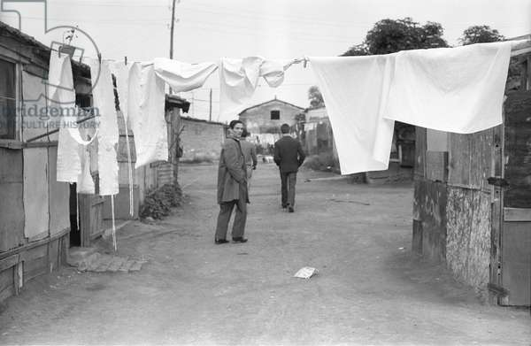 Pier Paolo Pasolini among the shacks with the boys from the township of Centocelle, Italy, 1960 (b/w photo)