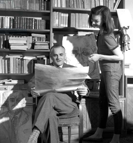 Rome, January 1956. The writer Alberto Moravia in his house looks at a portrait of him just drawn by model Ivy Nicholson