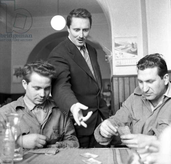 Roma, 1956. Il regista Pietro Germi, maestro del neorealismo italiano, assiste a una partita di carte in un'osteria