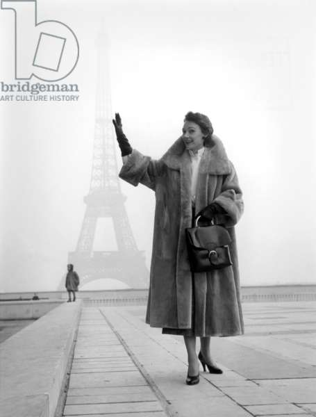 "Paris, 1952. Model Sophie Malga' walking around the city holds with one hand the Eiffel tour that emerges from the shadows. This picture comes from the reportage ""The Day of a Model"""