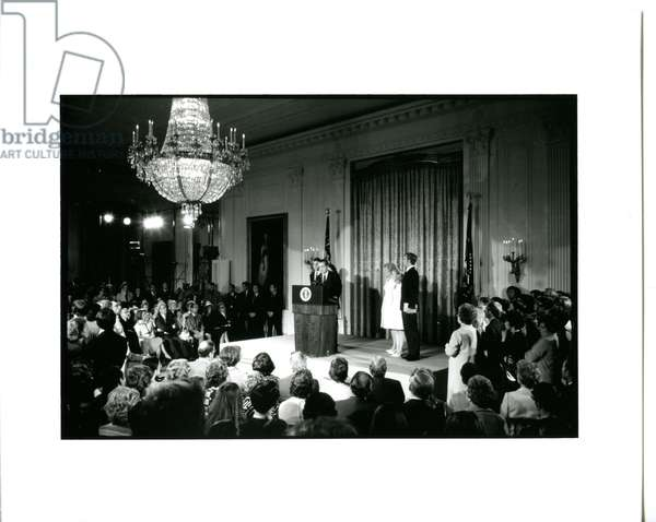 President Nixon, attended by his wife and family, addressing members of his cabinet and the White House staff during his farewell in the East Room of the White House, August 9, 1974 (b/w photo)