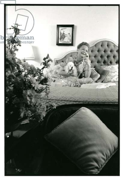 Martha Mitchell, and her poodle Buttons, telephoning from her Watergate apartment bedroom, March 1971 (b/w photo)
