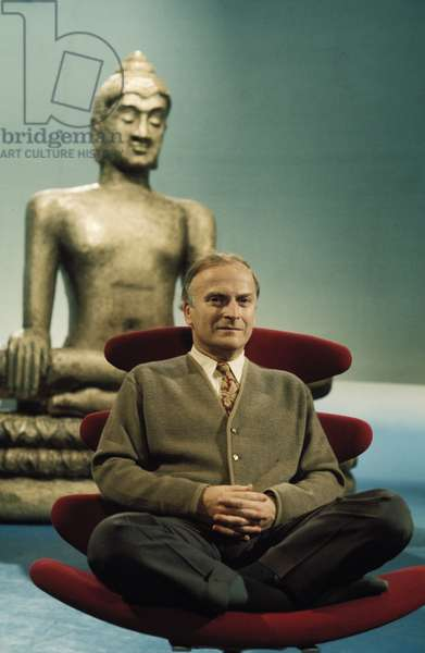Yehudi Menuhin sitting with folded legs in front of Buddha statue, circa 1970