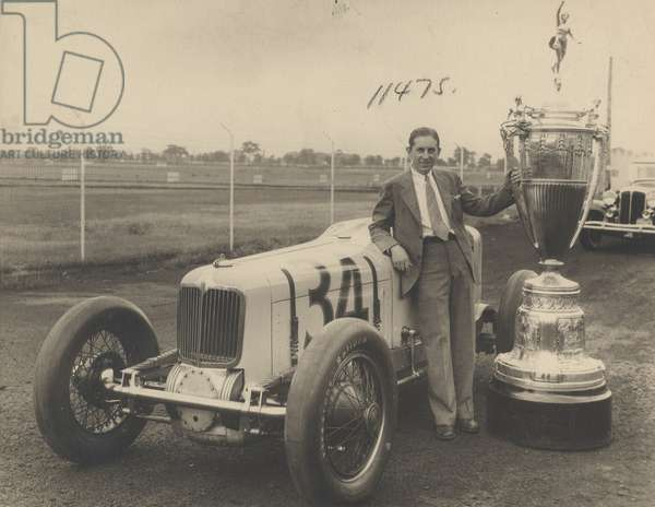 Harry Hartz standing alongside of Indianapolis trophy awarded him for his car winning 3 successive championships at Indianapolis, 1932 (b/w photo)
