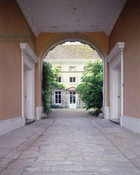 The Tudor courtyard of Firle Place, Sussex, seen through the entrance archway (photo)