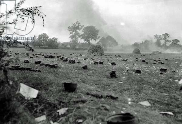 A French field full of German helmets, Normandy, France, June 1944 (b/w photo)