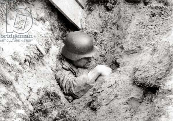 A German soldier has survived being partly buried during an Allied bombing, Quinéville, Normandy, France, June 1944 (b/w photo)