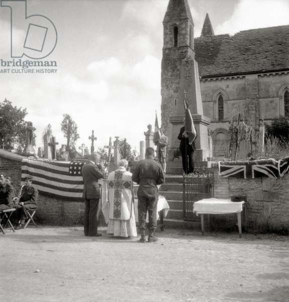 Mass is celebrated in the open air in front of the Church of St. Ouen, at the foot of the memorial in the presence of civilians and Canadian soldiers of the 2nd Canadian Infantry Division, Rots, Normandy, France, 14th June 1944 (b/w photo)
