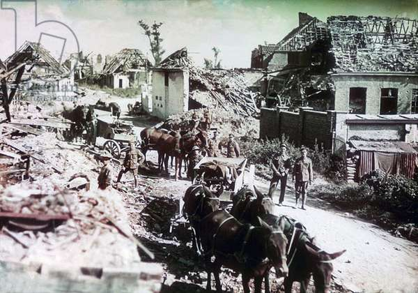 Soldiers, mules and carts in the ruined village of Voormezeele, south of Ypres on the Western Front, Belgium, August 1917 (colour Paget plate)