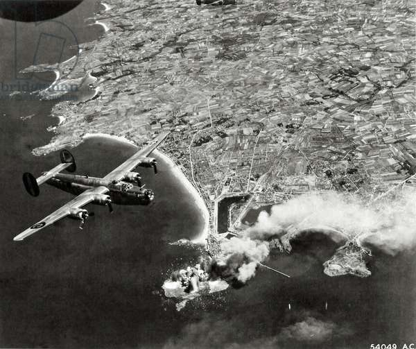 """A Boeing B-24 """"Liberator"""" (Lockheed Consolidated B-24 Bomber) is above the city which is on fire, Saint-Malo, Brittany, France, June 1944 (b/w photo)"""