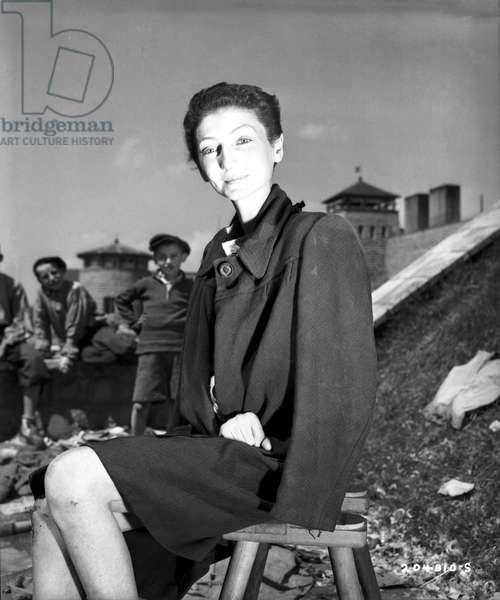 The Hungarian Jewish stage actress from Budapest, Livia Nador, sits outside on a stool at Gusen concentration camp after liberation by US forces, 6th May 1945 (b/w photo)