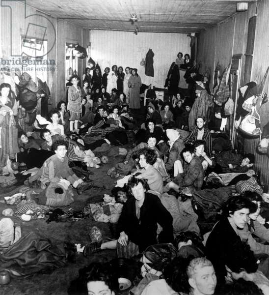 Gypsy (Roma and Sinti) women in a barrack block with no bunks in Bergen-Belsen concentration camp after it had been turned over to the Allied 21st Army Group, 15th April 1945 (b/w photo)