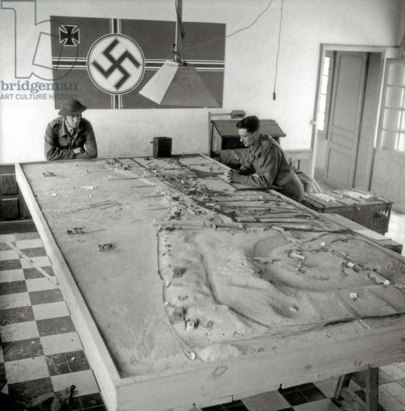 Two Canadian soldiers look at a German model of the area around Widerstandsnest 29 (Wn29) and the mouth of the Seulles as well as Widerstandsnest 31 (Wn31), Courseulles-sur-Mer (Juno Beach), Normandy, France, June 1944 (b/w photo)