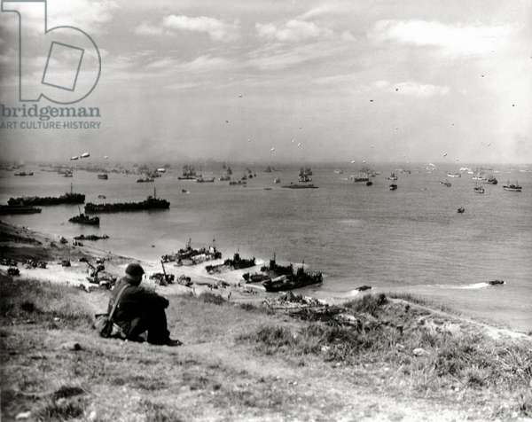 A man sitting above Omaha watching the ships, Omaha Beach, Normandy, France, June 1944 (b/w photo)