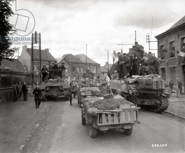 Civilians and American vehicles including tanks are in the street on the day of liberation of the town, Louvroil, Normandy, France, 2nd Sepember 1944 (b/w photo)