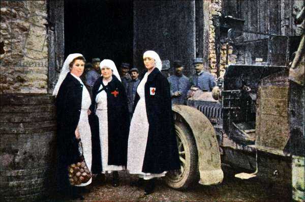 Three women wearing the Red Cross and the French ambulance staff with a vehicle, Verdun, September 1916 (autochrome)