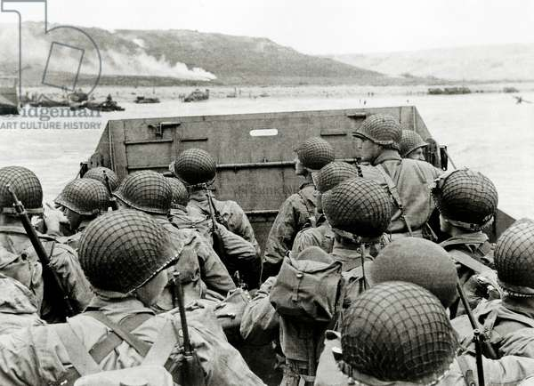U.S. soldiers watch the Normandy coast from a Landing Craft  Vehicle, Personnel (LCVP) heading towards Omaha Beach Easy Red sector, Colleville-sur-Mer, Normandy, France, 6th June 1944 (b/w photo)