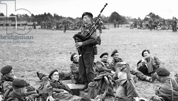 Bill Millin, best remembered for playing the pipes while under fire during the D-Day landing, Sword Beach, Normandy, France, June, 1944 (b/w photo)