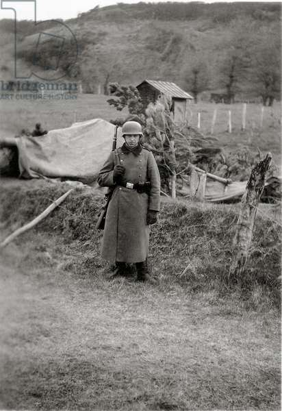 A helmeted and gloved German sentry is on duty outside next to a gun concealed with a tarp and pine branches, Normandy, France, 1944 (b/w photo)
