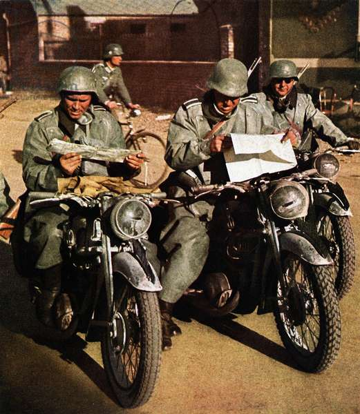 Three German soldiers of the Wehrmacht on motorcycles studying road maps, France, June 1940 (photo)