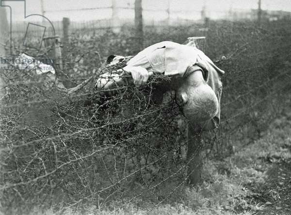The corpse of a prisoner lies on the barbed wire fence in Leipzig-Thekla, a sub-camp of Buchenwald, near Weimar, Germany, 19th April 1945 (b/w photo)