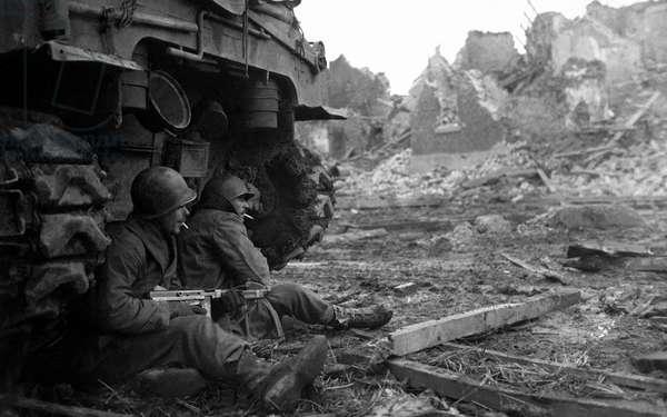 Two American GIs from the 9th Infantry Division shelter beneath a Sherman M4 tank, Geich near Düren, Germany, 11th December 1944 (b/w photo)