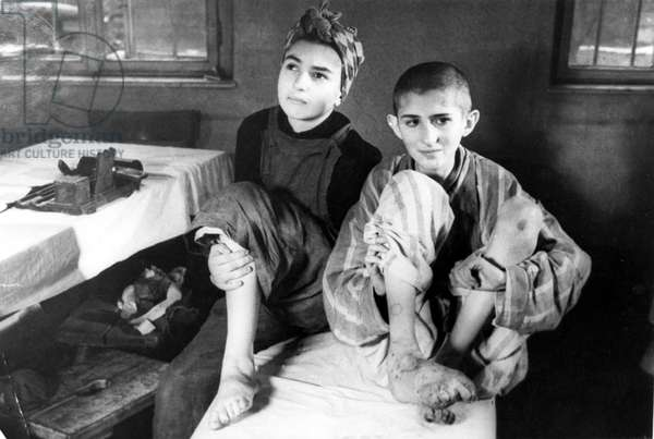 Two children in the medical station at Auschwitz concentration camp, February 1945 (b/w photo)