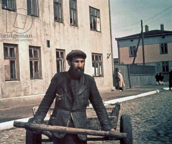 A man carrying goods using a hand cart in the Lodz (Litzmannstadt) ghetto, Lodz, Poland, 1941 (photo)