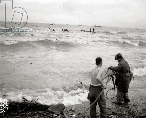 Three Engineers prepare a rope to support a shipwrecked soldier near Omaha Beach, Easy Red sector, Colleville-sur-Mer, Normandy, France, 6th June 1944 (b/w photo)