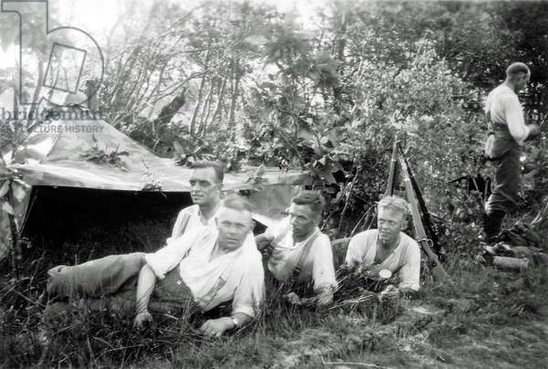 Five young soldiers of the Wehrmacht with a tent in the forest, France, 1944 (b/w photo)