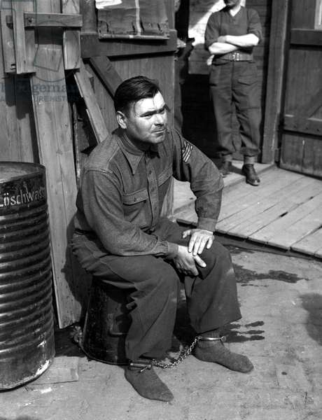 Commandant Josef Kramer with his feet shackled being guarded by a British soldier before being taken to a prison cage, Bergen-Belsen concentration camp, 15th April 1945 (b/w photo)