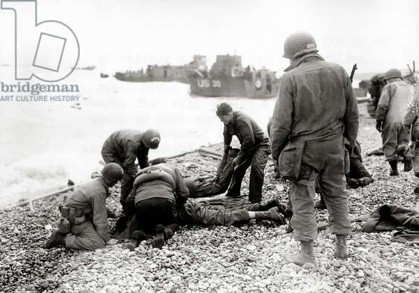 On a pebble beach at Omaha Beach, U.S. soldiers deal with injuries, Colleville-sur-Mer, Normandy, France, 6th June 1944 (b/w photo)