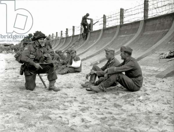 Corporal Victor Deblois from the 3rd Canadian Infantry Division crouching weapon in hand before two German prisoners sitting at the foot of the concrete dam at Juno Beach, Bernières-sur-Mer, Normandy, France, 6th June 1944 (b/w photo)