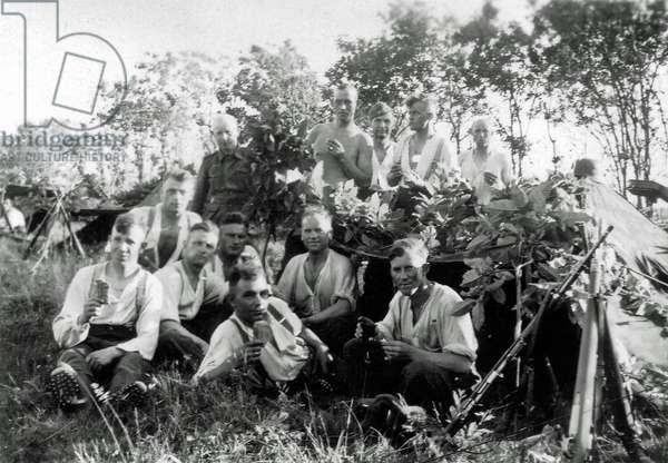 Twelve young soldiers of the Wehrmacht with a tent in the forest, France, 1944 (b/w photo)