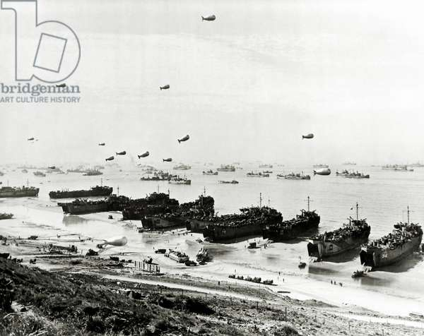In front of the landing beach huge Landing Ships, Tank (LST) unload large quantities of vehicles and equipment, Omaha Beach, Colleville-sur-Mer, Normandy, France, 9th June 1944 (b/w photo)