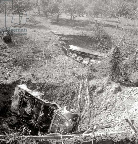 In an orchard there are two bomb craters with vehicles, south of Vimoutiers, Normandy, France, August 1944 (b/w photo)