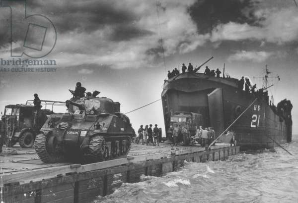 "The U.S. Coast Guard manned USS LST-21 unloads British Army tanks and trucks onto a ""Rhino"" barge during the early hours of the invasion on Gold Beach, Normandy, France, 6th June 1944 (b/w photo)"