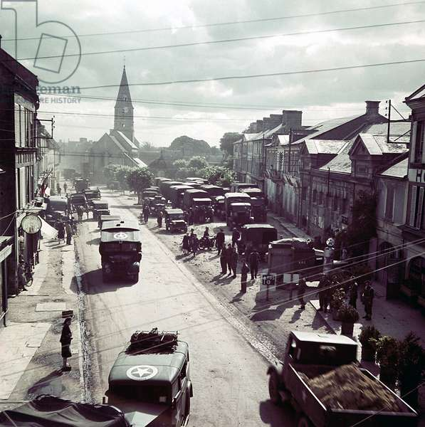 United States Army trucks, jeeps and other vehicles entering a town in Normandy, France, June 1944 (photo)