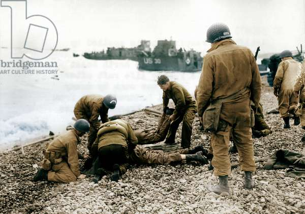 On a pebble beach at Omaha Beach, U.S. soldiers deal with injuries, Colleville-sur-Mer, Normandy, France, 6th June 1944 (photo)