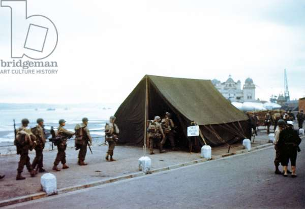 Soldiers checking their assignments in a tent near the port at Weymouth, Southern England, June 1944 (photo)