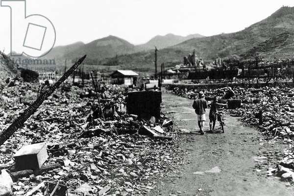 People walk through the charred ruins of Nagasaki, shortly after an atomic bomb has destroyed the city, Japan, August 1945 (b/w photo)