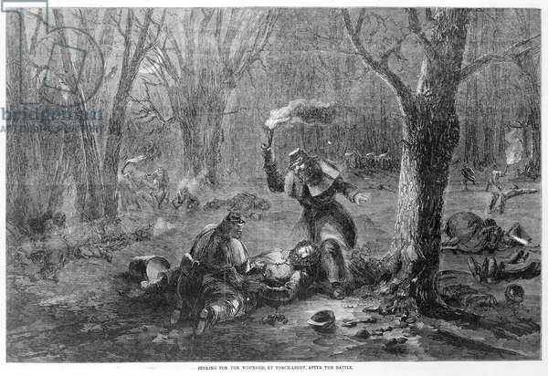 CIVIL WAR: WOUNDED Searching for the wounded by torchlight after the Battle of Fort Donelson in 1862 during the Civil War. Woodcut.
