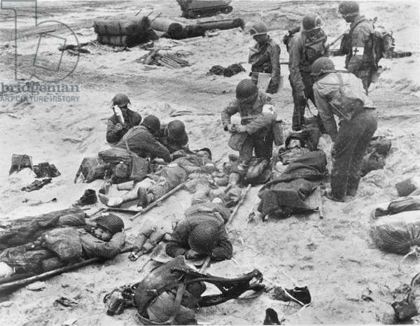 WORLD WAR II: D-DAY, 1944 American medics administer first aid to soldiers wounded in the initial attack at Omaha Beach during the invasion of Normandy, France, 9 June 1944.
